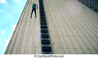Fearless man descend down with cord on skyscraper wall. Blue...