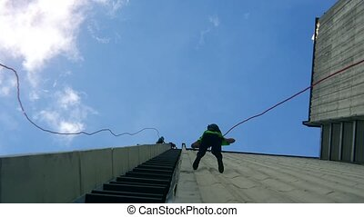 Fearless people descend down with safety rope on skyscraper...