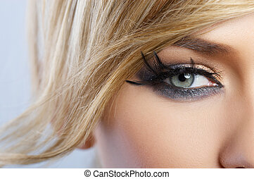 Beautiful blond woman with artistic feather makeup