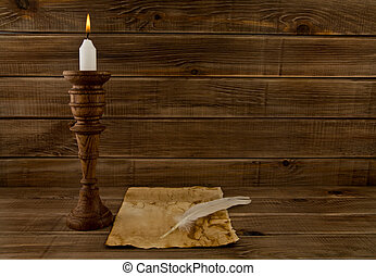 feather, old paper and candle