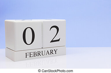 February 02st. Day 02 of month, daily calendar on white table with reflection, with light blue background. Winter time, empty space for text