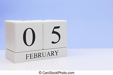 February 05st. Day 05 of month, daily calendar on white table with reflection, with light blue background. Winter time, empty space for text