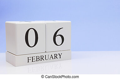 February 06st. Day 06 of month, daily calendar on white table with reflection, with light blue background. Winter time, empty space for text