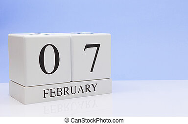 February 07st. Day 07 of month, daily calendar on white table with reflection, with light blue background. Winter time, empty space for text