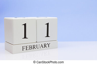 February 11st. Day 11 of month, daily calendar on white table with reflection, with light blue background. Winter time, empty space for text