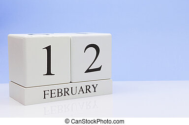 February 12st. Day 12 of month, daily calendar on white table with reflection, with light blue background. Winter time, empty space for text