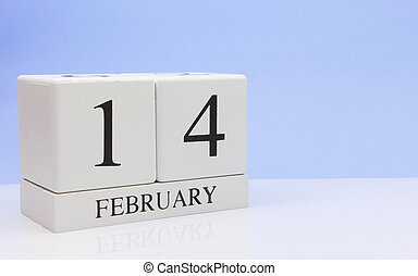 February 14st. Day 14 of month, daily calendar on white table with reflection, with light blue background. Winter time, empty space for text