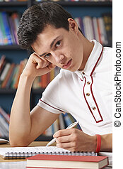 Fed Up Male Teenage Student Working In Library