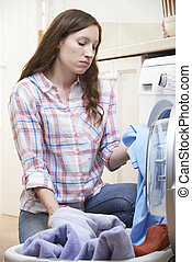 Fed Up Woman Doing Laundry At Home