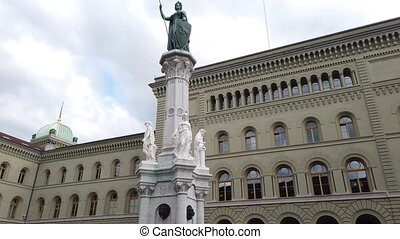 The west wing of Federal Palace, Swiss Parliament building and Bernabrunnen fountain and statue representing city of Bern and canton of Bern, Switzerland. Landmark of historical old town.