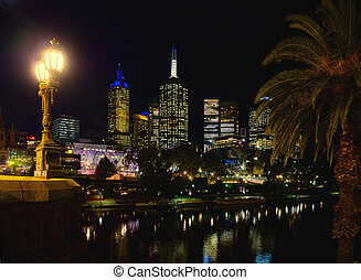 Federation square in Melbourne at night, over the Yarra -...