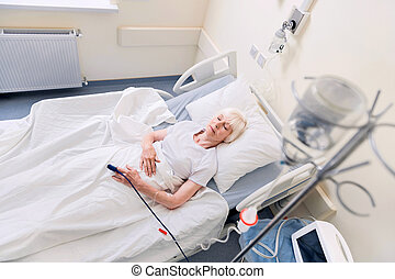 Feeble senior woman resting while recovering - In hospital....