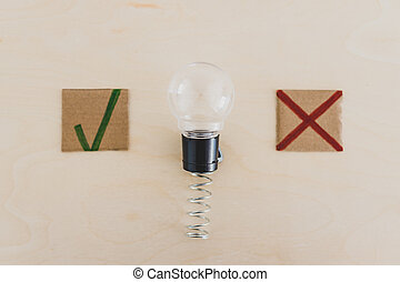 feedback about good and bad ideas, lightbulb on spring with green tick and red cross