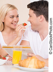 Feeding him with berry. Young loving couple looking at each other while having breakfast together