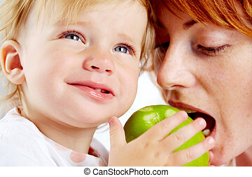 Portrait of female ready to bite ripe apple in her child hands