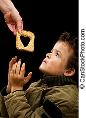 Feeding the poor concept with dirty kid receiving slice of bread - on black