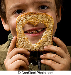 Feeding the poor - kid holding a slice of bread with dirty hands smiling happily