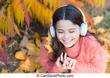 Feel joy. Kid girl relaxing near autumn tree with headphones. Music for autumn cozy mood. Autumn playlist concept. Enjoy music outdoors fall warm day. Listening song. Audio file. Educational podcast
