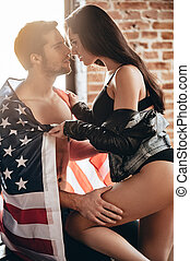 Feel the freedom! Side view of beautiful young woman with perfect buttocks adjusting American flag on her boyfriend shoulders and leaning to him