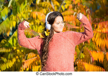 Feel the vibe. Music for autumn mood. Listening song. Enjoy music fall day. Listening audio best way help child improve vocabulary. Kid girl near tree with headphones. Autumn walks with nice songs