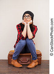 Feeling bored.  Beautiful young woman in headwear holding hands on chin and looking away while sitting on suitcase