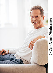 Feeling calm and relaxed. Side view of cheerful mature looking at camera and smiling while sitting on the couch at home