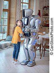 Girl in orange shirt feeling good with her house robot
