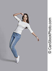 Feeling comfortable in her style. Full length of attractive young woman in casual wear posing while standing against grey background