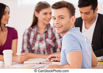 Feeling confident about his final exam. Four cheerful students sitting together at the desk and studying while one man looking over shoulder and smiling