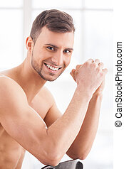 Feeling confident. Side view of handsome young muscular man sitting on the chair and smiling at camera