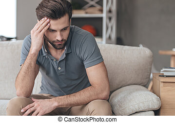 Feeling depressed. Desperate young man keeping his hand on forehead while sitting on the couch at home