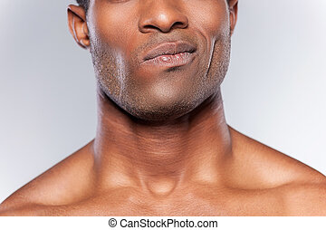Feeling doubt. Cropped image of young African man grimacing while standing against grey background