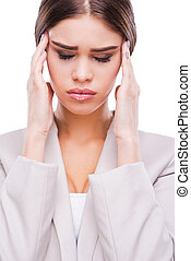 Feeling exhausted. Depressed young businesswoman touching her face and keeping eyes closed while standing against white background