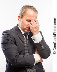 Feeling exhausted. Side view of young man in shirt and tie touching his nose