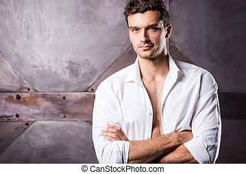 Feeling flirty. Handsome young man in unbuttoned shirt ...