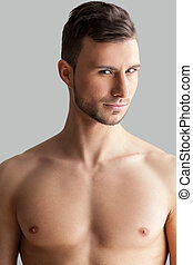 Feeling flirty. Handsome young muscular man looking at ...
