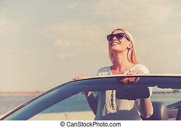 Feeling freedom. Beautiful young woman in eyewear enjoying road trip while standing up in white convertible