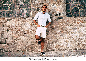 Feeling good and looking great. Full length of handsome young African man in smart casual clothes holding hands in pockets and smiling while leaning at the stoned wall outdoors
