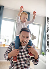 Cute little girl sitting on her fathers shoulders
