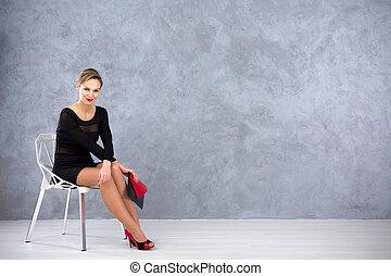 Very attractive elegant woman sitting on a silver gap chair by a grey stucco wall