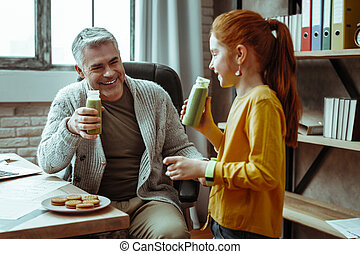Cheerful positive man smiling to his daughter