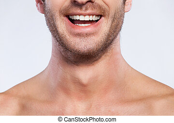 Feeling happy. Cropped image of handsome young shirtless man smiling while isolated on grey background