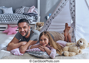 Feeling happy together. Father and his daughter smiling and...