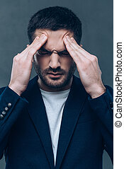 Feeling headache. Portrait of frustrated young man touching his head with hands while standing against grey background.