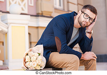 Feeling hopeless about her come. Frustrated young man in smart jacket leaning his head on hand while sitting on the bench with a bouquet of flowers laying near him