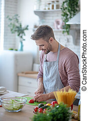 Smiling bearded man feeling joyful while cooking salad