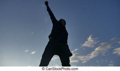Feeling like a winner Silhouette hand up of man pumping his fist in the air. man victory businessman lifestyle concept