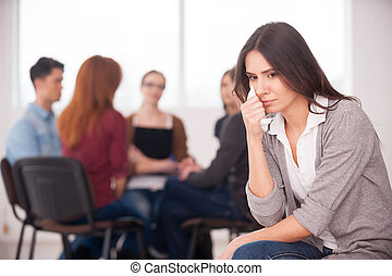Feeling lonely and depressed. Depressed young woman sitting at the chair and crying while other people communicating on background