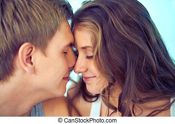 Feeling of love - Young couple touching by their faces