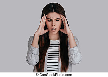 Feeling pain. Frustrated young woman in smart casual wear...